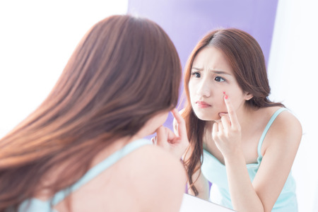 Face Skin Problem - skin care woman unhappy touch her acne and look mirror. asian beauty Standard-Bild