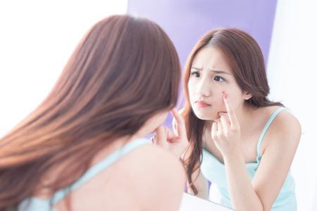 Problème de la peau du visage - soins de la peau femme malheureuse toucher son acné et miroir de look. asiatique beauté