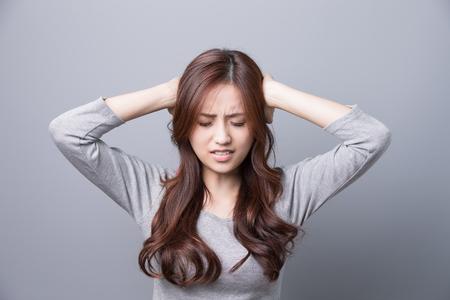 Una mujer sienta dolor de cabeza, enfermedad, belleza asiática, fondo gris Foto de archivo