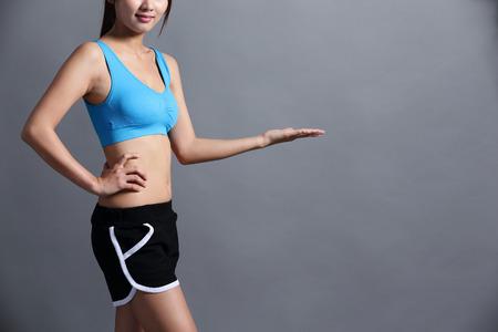 cintura: Deporte de la mujer con la figura de la salud y se muestran somthing a usted aislados sobre fondo gris, perfecto para su diseño o texto, belleza asiática