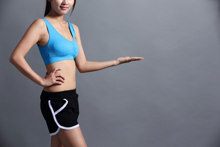 asia women: Sport Woman with health figure and she show somthing to you isolated over gray background, great for your design or text, asian beauty Stock Photo
