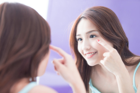 Femme face et soin des yeux et elle touche l'?il aux mains, elle regarde le miroir. Beauté asiatique Banque d'images