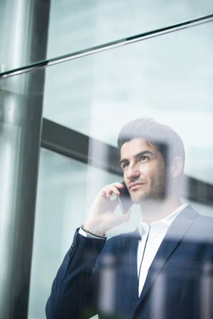 hablando por telefono: Business man talking on smart phone in front of the office window