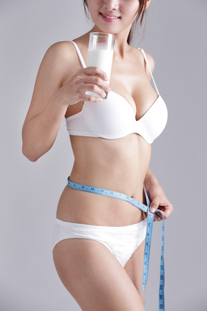 Milk and Health woman body - Woman measuring shape of beautiful waist for Healthy lifestyles concept with gray background, asian beauty Stock Photo - 55825653