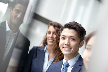 business team: Business people team meeting in front of the office window, asian and caucasian