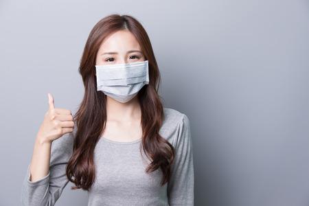mujer alegre: Una mujer lleva una máscara y el pulgar, la enfermedad, la belleza asiática, fondo gris