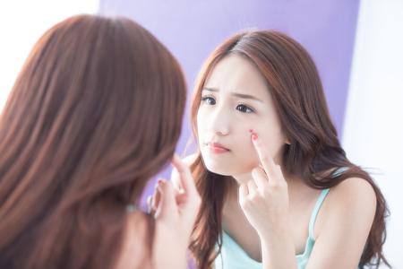 piel: Cara de problemas de la piel - mujer infeliz cuidado de la piel toque su acné y espejo mirada. belleza asiática