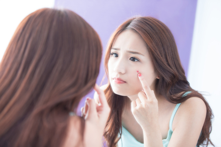 Face Skin Problem - skin care woman unhappy touch her acne and look mirror. asian beauty Foto de archivo