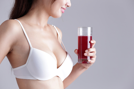 beauty body: red cranberry for Health concept - Beautiful slim body of woman and orange juice isolated on gray background Stock Photo