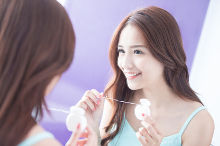 floss: Close up of Smile woman clear teeth by floss and look mirror. great for health dental care concept. asian beauty
