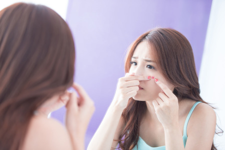 woman mirror: Face Skin Problem - skin care woman unhappy touch her acne and look mirror. asian beauty Stock Photo