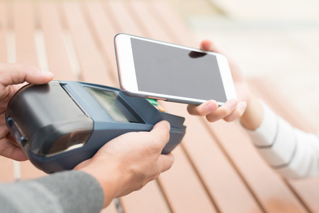 contactless: Customer pay by cellphone, great for your design Stock Photo