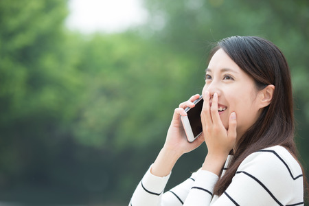 call of nature: Happy woman speak and use smart phone outdoor, asian beauty