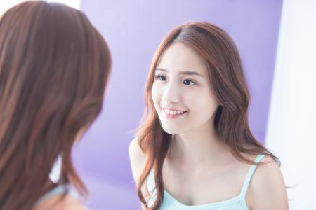La mujer hermosa cuidado de la piel y ver sonreír espejo. belleza asiática Foto de archivo