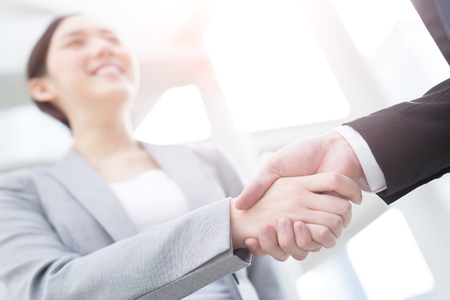 アジアの街の背景が付いているオフィスの成功ビジネス人チームのグループが手を振る