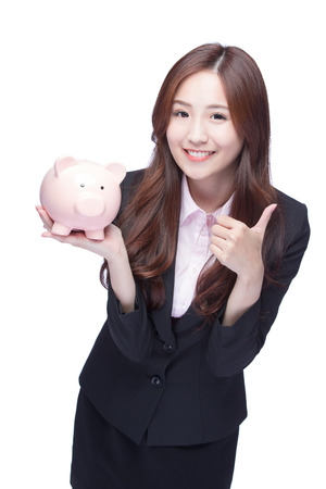 investment concept: Happy business woman smiling holding pink piggy bank and show thumb up isolated on white background. Asian girl Stock Photo