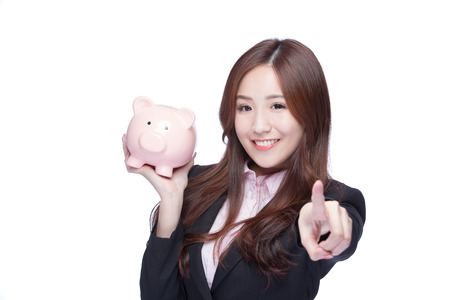 chinese lady: business woman smiling holding pink piggy bank and pointing to you isolated on white background. Asian girl Stock Photo