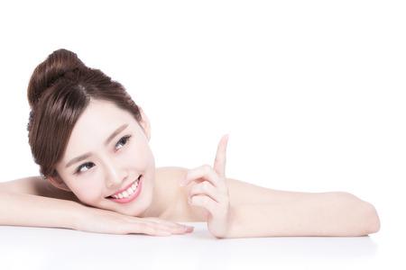 Mujer encantadora sonrisa y mostrar algo mientras mentiroso aislado en el fondo blanco, chica asiática