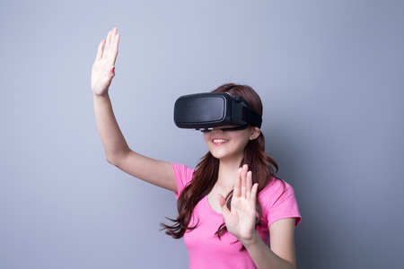 Smile happy woman getting experience using VR-headset glasses of virtual reality at home much gesticulating hands, asian beauty