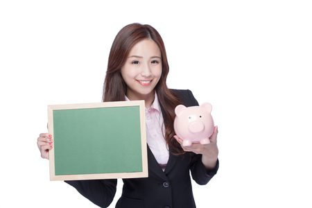 business money: smile young business woman hold chalkboard and piggy bank at white background, business concept, asian beauty