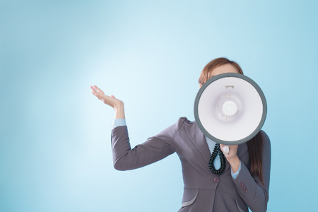 executive woman: Business woman happy with a megaphone isolated on blue background, model is a asian beauty