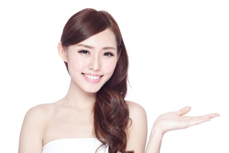 Beauty woman show something to you with charming smile, health skin, teeth and hair isolated on white background, asian beauty