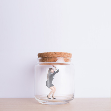 pent: business woman imprisoned in jar with white wall background, great for your design or text, asian Stock Photo