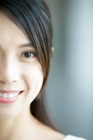 half: young health woman smile to you. half face, with health teeth and skin, asian beauty