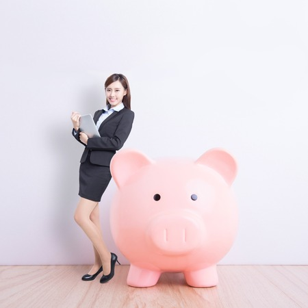 invest: business woman lean pink piggy bank and use digital tablet pc with white wall background, great for your design or text, asian