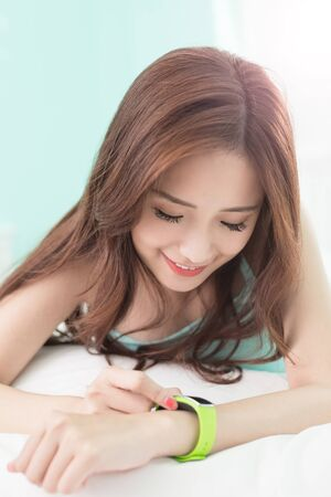 wellness sleepy: Charming woman look wearable smart watch and smile lying on the bed, asian girl Stock Photo