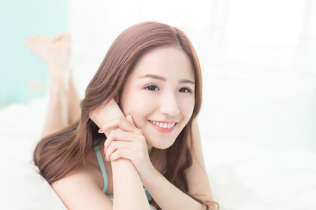 wellness sleepy: Health woman Smile to you and she lying on the bed in the morning , asian girl