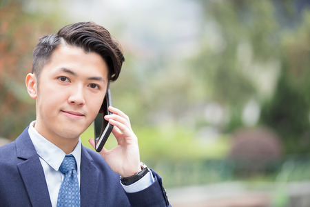 asian business man: Business man talking on smart phone with green background in the park, asian
