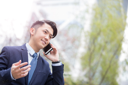 business asia: Business man talking on smart phone with business office building background, asian Stock Photo