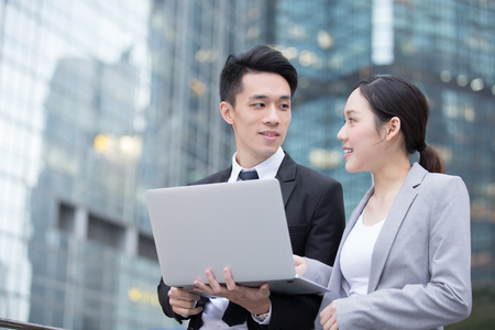 young executive: Business people team meeting with computer in front of the office building, shot in Hong Kong, asian