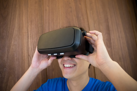 virtual reality simulator: Smile happy man getting experience using VR-headset glasses of virtual reality at home much gesticulating hands, asian male