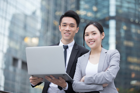Business people team meeting with computer in front of the office building, shot in Hong Kong, asian