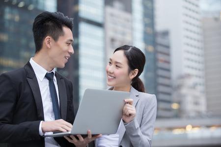 La gente de negocios de las personas Reunión con el ordenador delante del edificio de oficinas, rodado en Hong Kong, asiático