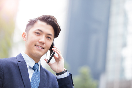 hongkong: Business man talking on smart phone with business office building background, asian Stock Photo