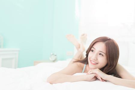Zdravotní žena úsměv na vás a ona leží na posteli v dopoledních hodinách, Asiatka