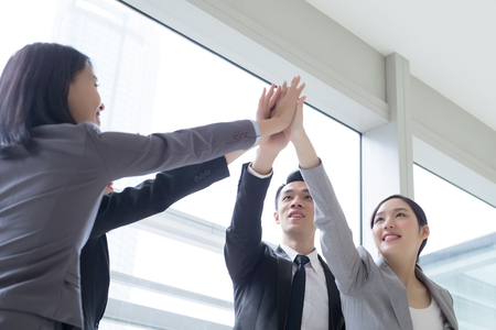 Business people team smile give high five in the office, shot in Hong Kong, asian woman and man