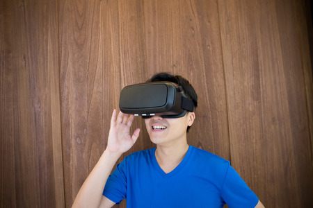Smile happy man getting experience using VR-headset glasses of virtual reality at home much gesticulating hands, asian male