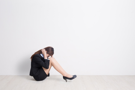 overwork: business woman feel unhappy with white wall background, great for your design or text, asian