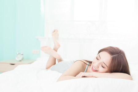 wellness sleepy: Health woman Smile feel carefree and she lying on the bed in the morning , asian girl Stock Photo