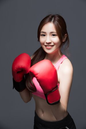 beat women: sport woman is boxing isolated on the gray background,asian Stock Photo