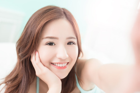 Gesundheit Frau Lächeln ein selfie nehmen und sie zu Hause auf dem Bett liegend, asiatische Mädchen