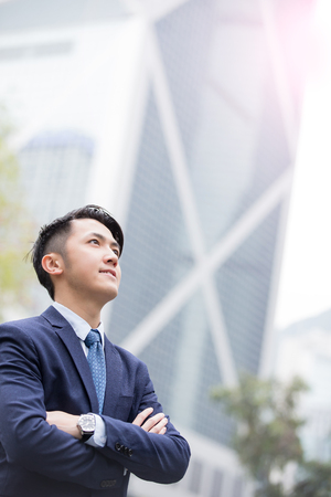businessman in office: Business man smile look sky with business office building background, asian, shot in Hong Kong