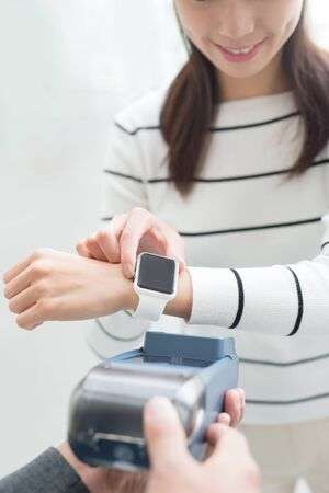 business finance: young woman pay by smart watch with empty screen, great for your design,asian beauty