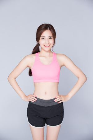 Sport meisje op een grijze achtergrond. Running fitness sport vrouw lachend blij. Aziatische schoonheid Stockfoto