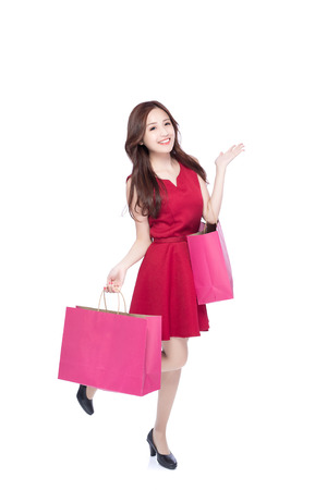 happy shopping young woman show something - isolated on white background, full body, asian beauty Stock Photo