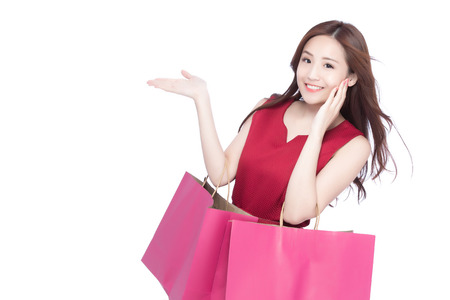 happy shopping young woman show something - isolated on white background, asian model beauty